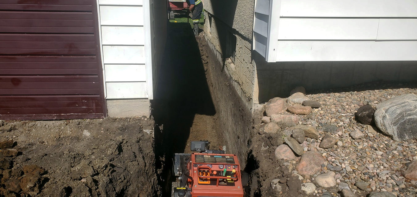 Trench dug between two houses to run sewer and water mains.